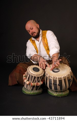 Mature exotic darabuka drummer with two drums. percussion. black background - stock photo
