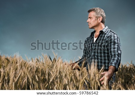 Mature farmer looking with satisfaction at his cultivated field and having care of wheat after a working day, dramatic sky - stock photo