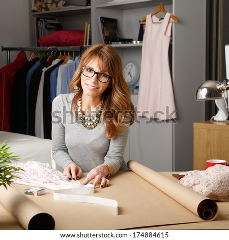 Mature fashion designer working in her studio.