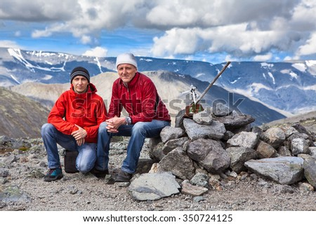 Mature father and adult son sitting on the mountain pass, wearing red jackets