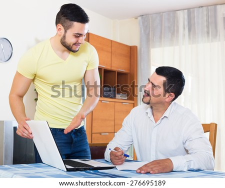 Mature father helping happy adult son to fill application form - stock photo