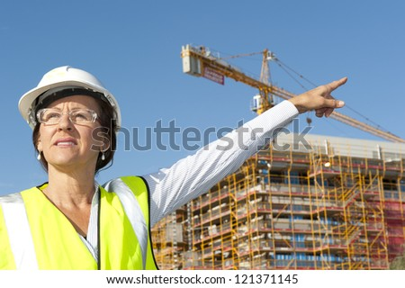 Mature female architect or construction engineer on building site supervising, wearing hardhat, with blurred background of construction site with crane. - stock photo
