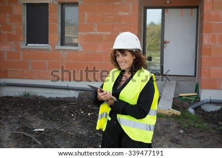 Mature female architect or construction engineer on building site supervising, wearing hardhat, with blurred background of construction site  - stock photo