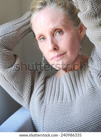 Mature female blond beauty expressions indoors. - stock photo