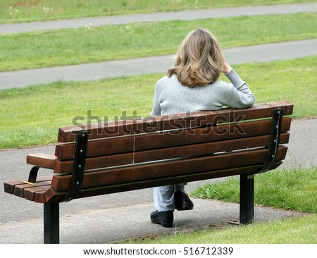 Mature female blond beauty sitting on park bench outside.