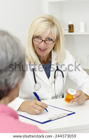 Mature female blond haired  doctor sitting at the desk and talking with her senior patient. - stock photo