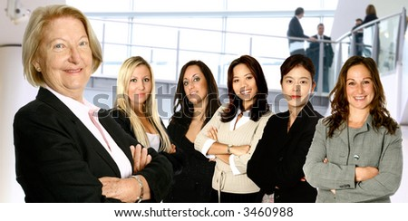 Mature female caucasian  leading a team of business women from diverse background made up of a caucasian, a mediterranean, an Asian and a Japanese woman, in corporate interior lobby. - stock photo