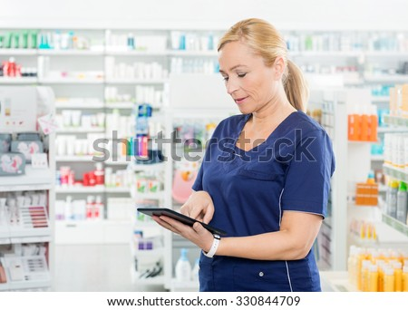 Mature female chemist using digital tablet while standing in pharmacy - stock photo