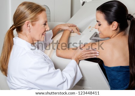 Mature female doctor assisting young patient during mammography - stock photo