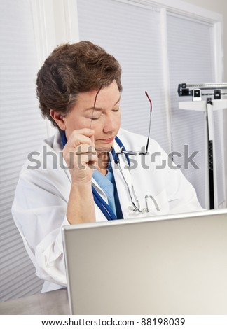 Mature female doctor or nurse in blue scrubs and lab coat, working on laptop, holding glasses, looking serious, stressed and competent. - stock photo