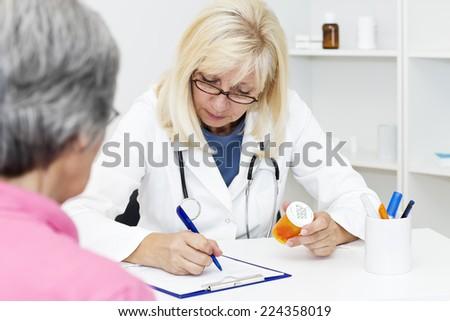Mature female doctor prescription medicine to  her senior patient.   - stock photo
