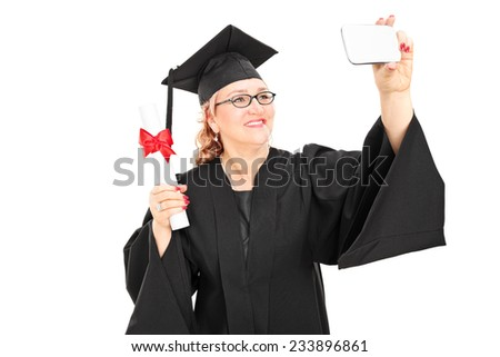 Mature female graduate taking a selfie with cell phone isolated on white background
