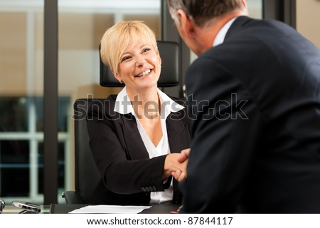 Mature female lawyer or notary with client in her office - handshake - stock photo