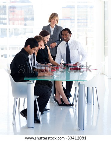 Mature female manager with her team in office - stock photo