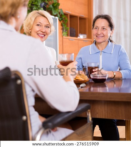 Mature female pensioners drinking tea with handicapped friend. Focus on the left woman - stock photo