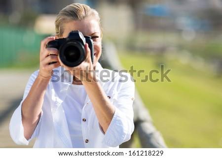 mature female photographer taking photos outdoors - stock photo