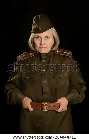 Mature female soldier on a black background - stock photo