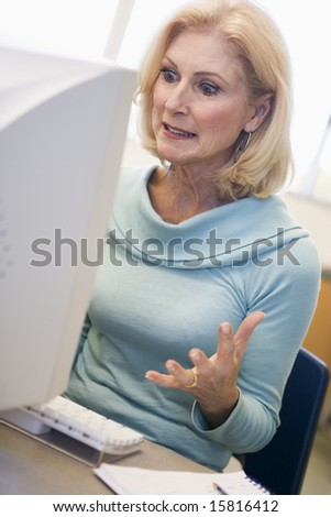 Mature female student expressing frustration at computer - stock photo