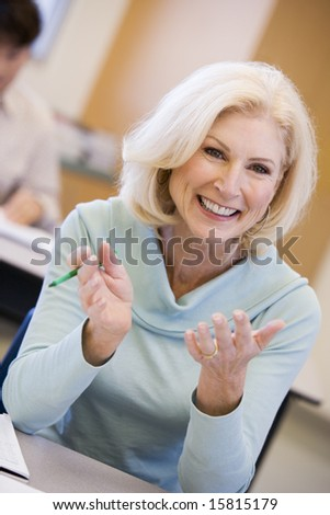 Mature female student gesturing in class - stock photo