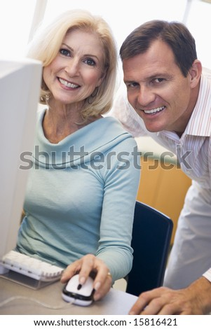 Mature female student learning computer skills - stock photo