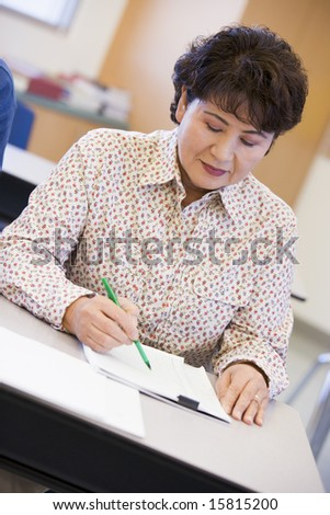 Mature female student writing in class - stock photo