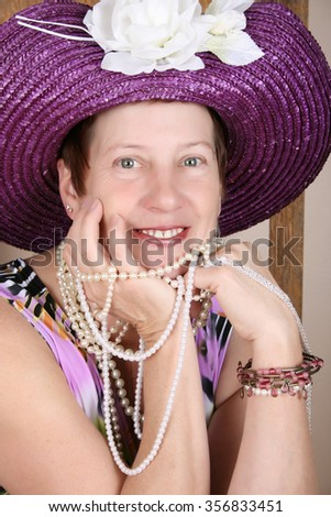 Mature female wearing a purple hat and jewellery - stock photo