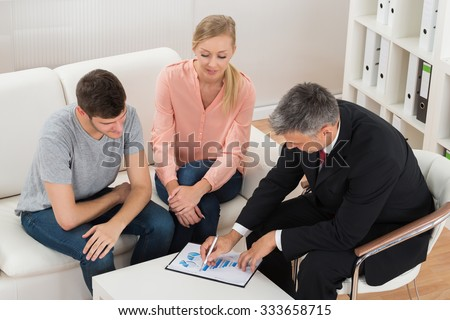 Mature Financial Advisor Showing Graph On Paper To Young Couple - stock photo