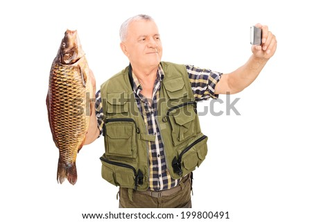 Mature fisherman holding a fish and taking selfie isolated on white background - stock photo