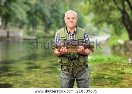 Mature fisherman standing in river and holding a fish outdoors - stock photo