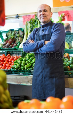 Mature friendly cheerful seller offering seasonal vegetables in local grocery