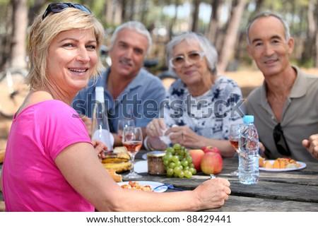Mature friends eating alfresco - stock photo
