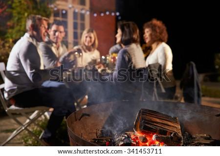 Mature Friends Enjoying Outdoor Evening Meal Around Firepit - stock photo