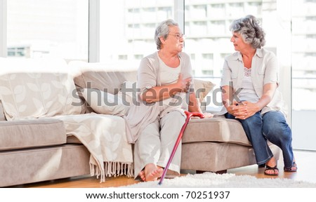 Mature friends talking on the sofa - stock photo
