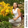 Mature gardener  in flower bed with bouguet of orange lilies - stock photo