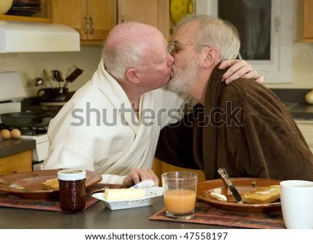 Mature gay couple kissing at breakfast - stock photo