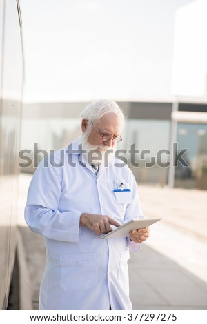 Mature general practitioner using digital tablet outdoors - stock photo