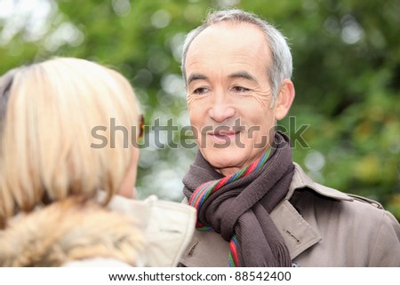 mature gentleman looking at his lady fondly - stock photo