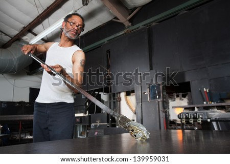 Mature glass artisan turning rod with small vase - stock photo