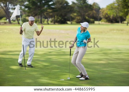 Mature golfer couple celebrating success while standing on field