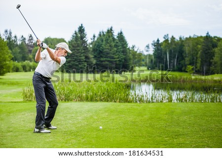 Mature Golfer on a Golf Course Taking a Swing on the Start - stock photo