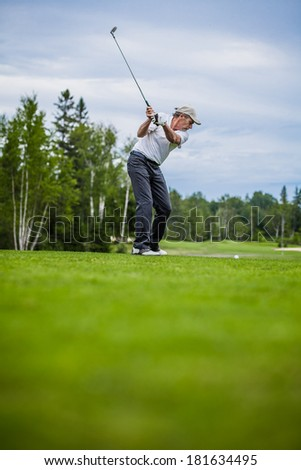 Mature Golfer on a Golf Course Taking a Swing on the Start (with room for your text)