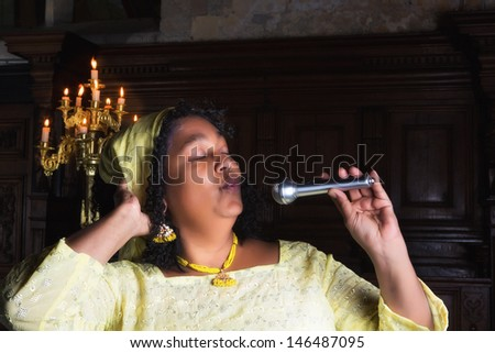 Mature gospel singer with microphone singing during mass - stock photo