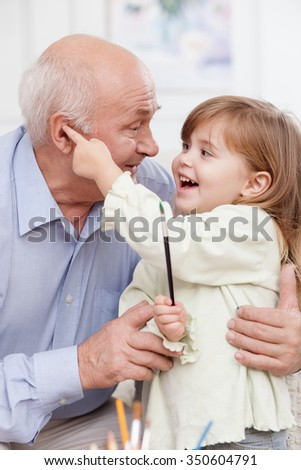 Mature grandfather is taking care of small granddaughter. He is embracing her and smiling. The girl is stretching finger to male ear and holding a paintbrush - stock photo