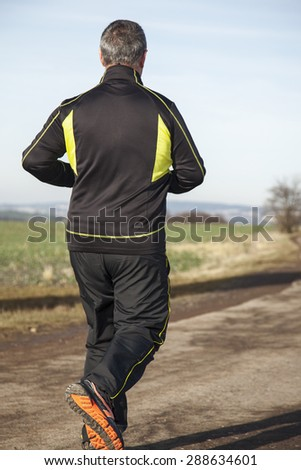 Mature gray haired man while jogging - stock photo