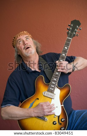 Mature guitarist with sunburst hollow body guitar searching for the high notes - stock photo
