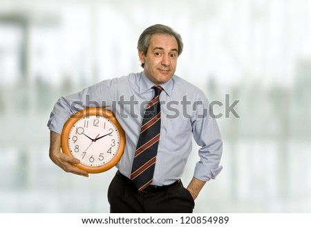 mature handsome business man holding a clock - stock photo