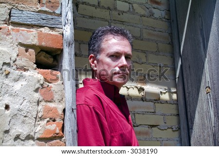 Mature, handsome, caucasian male looking with a very steely gaze surrounded by dilapidated brick walls and an old weathered wooden section of wall. - stock photo