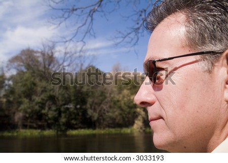 Mature, handsome, man smiling contentedly while enjoying the sunny weather and calm surrounding. - stock photo