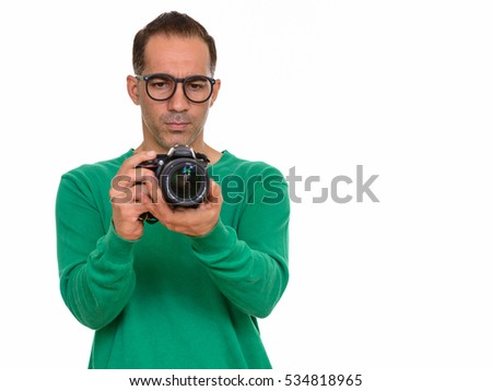 Mature handsome Persian man taking picture with camera