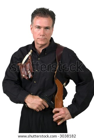 Mature, handsome, white male dressed in black on an isolated background wearing a shoulder holster armed with an automatic pistol. - stock photo